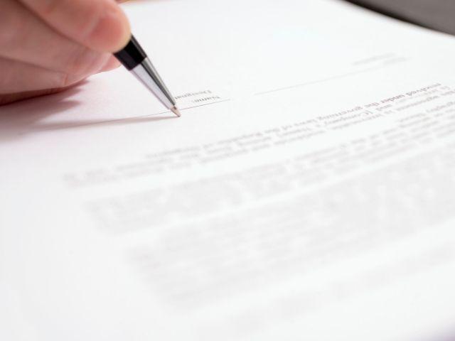 業務委託契約の書類にサインしている男性