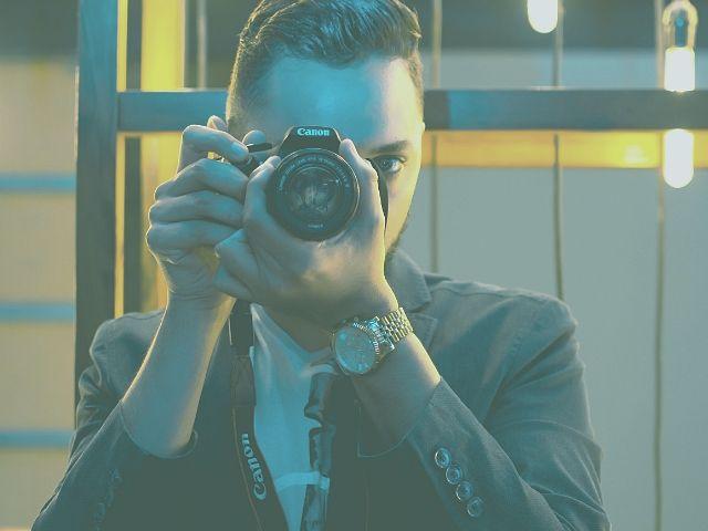 スーツで写真を撮るカメラマン